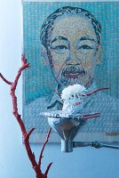 Oriental arrangement: red-painted branch and book on upturned lamp used as tray in front of large portrait
