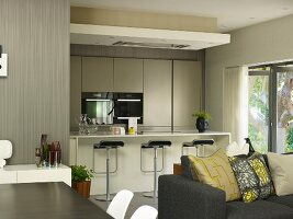 Dining area next to sofa with scatter cushions in front of open-plan fitted kitchen with designer bar stools at breakfast bar