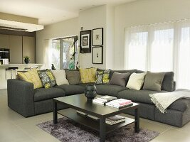 Coffee table in front of corner sofa with scatter cushions in open-plan interior