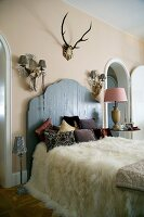 White fur blanket on French bed with rustic wooden headboard against wall with two sconce lamps and antlers