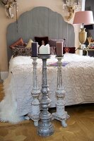 Floor-standing candlestick in front of French bed with wooden headboard next to bedside lamp with pink lampshade