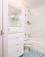 Washstand with large drawers and blue-green mosaic floor tiles in white bathroom
