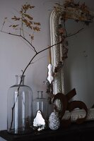 Christmas decoration hanging from branch in a large glass jar next to antique frame