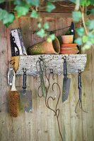 Gardening utensils on wall-mounted shelf made from a quarter-circle log, round hooks and metal brackets