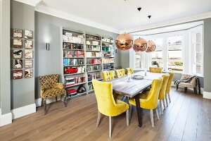 Room with bay window in English house; long table, yellow upholstered chairs, board floor and grey bookcases