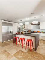 Designer kitchen with island counter, red bar stools, three designer pendant lamps, stone flagged floor and stainless steel fronts