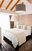 Double bed with upholstered headboard and pendant lamp with cylindrical lampshade in attic bedroom with sloping ceiling