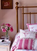 Scatter cushions with deep pink Toile de Jouy patterns on brass bed