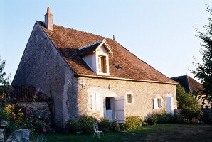 Old, French farm house with white window shutters in simple, one-storey stone facade