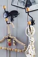 Metal wall hooks with round wooden ends on wooden wall and coathanger threaded with wooden beads