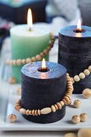 Various candles decorated with strings of wooden beads