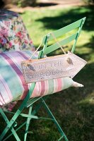 Striped cushion on pastel green garden chair with sign hanging on backrest