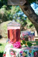 Floral tablecloth, refreshing drink in glass dispenser with tap and tray of glasses on garden table