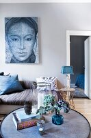 View past vase of flowers on round coffee table to couch below large portrait on wall painted pale grey