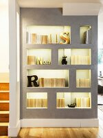 Modern grey wall with backlit shelving niches and partition screening staircase