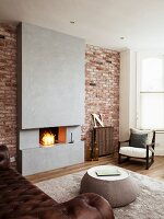 Coffee table in front of open fireplace in concrete chimney breast flanked by brick walls and armchair in corner