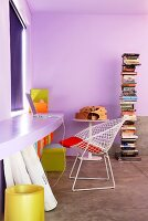 Interior painted lilac with curved desk in same shade along one wall and classic, white, wire-mesh chair