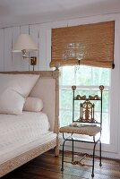 Delicate, ornate metal chair and antique bed with tall headboard next to window with half-closed, bamboo blinds