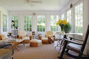 Verschiedene Stühle und Rattanstuhl Garnitur im Raum eines Anbaus mit Sprossenfenstern