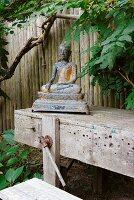 Buddhafigur aus Metall auf Vintage Werkbank in Freiem vor Holzzaun