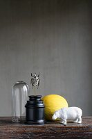 Still-life arrangement with white hippo ornament and scarab sculpture against black background
