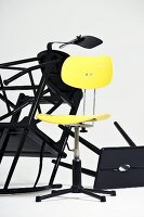 Yellow, retro swivel chair in front of tangle of toppled black wooden stools