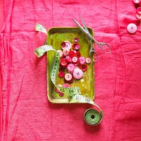 Red and pink buttons in metal dish with tape measure and scissors