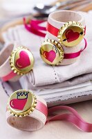 Gold bottle cap and heart motif and pink ribbons on wooden napkin rings