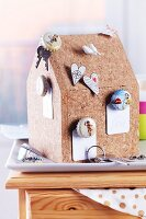 Cork model house used as pin board for upcycled bottle tops used as drawing pins