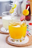 Glasses of orange and lemon drinks with straws decorated with the appropriate fruit motifs on bottle tops
