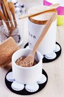 White-painted bottle tops stuck on black felt coasters arranged with simple, white sugar bowls and wooden spoons