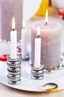 Various lit candles set on stacks or flat arrangements of bottle caps