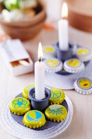 Simple candle stick and bottle caps painted yellow with various motifs arranged on white coaster