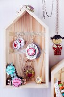Hand-crafted jewellery made from bottle tops in house-shaped jewellery rack