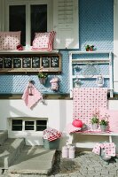 Red and white cushions and other country-style home accessories decoratively displayed for sale in front of pale blue wooden facade