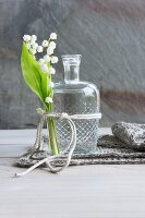 Lily of the valley tied to vintage glass bottle with cord