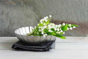 Lily of the valley in metal dish