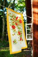 Floral tea towel hanging on washing line outside wooden cabin in woodland