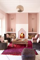 Armchairs around coffee table on magenta rug in front of open fireplace flanked by stacked firewood in elegant ambiance