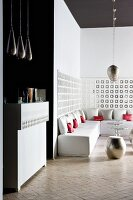 Counter and pendant lamps next to open-plan, minimalist lounge area with white, upholstered bench and metal stool