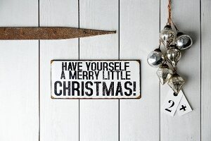 Sign (Have yourself a merry little Christmas) on wooden door next to baubles and tags