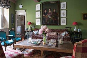 Rustikaler Couchtisch und verschiedene Stühle aus verschiedenen Stilen in grün getöntem, traditionellem Wohnzimmer mit Familienbild an Wand