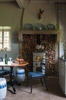 Runder Tisch und gepolsterter Stuhl vor Kaminofen mit Holzlager in ländlichem Esszimmer