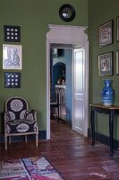 Durchgang mit weiss lackierter Holzverkleidung neben Sessel und Wandtisch vor Bildersammlung an grün getönter Wand