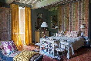 Chaiselongue gegenüber Stühlen und halbhohem Schrank an Bettende, daneben bodenlange gelbe Vorhänge am Fenster in ländlichem Schlafzimmer