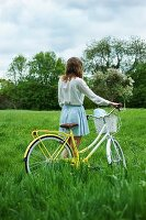 Girl with bicycle in green meadow