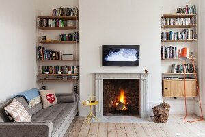 Cosy room in renovated period apartment with blazing open fire below flatscreen TV on wall flanked by symmetrical bookcases