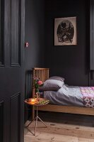 Black-painted bedroom with wooden bed, wooden floor and lit lamp and posy of roses on tray table
