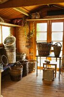 Collection of baskets on table and floor in wooden cabin