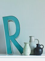 Letter ornament and collection of hand-made vases on surface